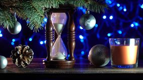Sand clock that indicates the time remaining until Xmas, toys of winter holidays. Xmas Decorations. Christmas background, a sand clock under a fir tree stock video