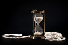 Sand clock and rope. On black background Royalty Free Stock Photo