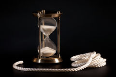 Sand clock and rope. On black background Stock Photo