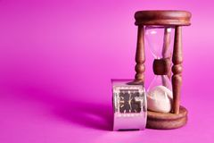 Sand clock. And a wristwatch, on a purple background with long shadows royalty free stock photo