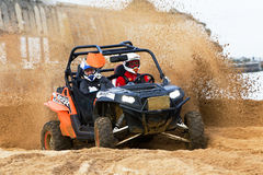 Sand cloud. RAMSGATE, UK - OCTOBER 20: An unnamed driver racing in the SXS class takes his Polaris RZR around a hairpin corner at speed during the QRA MCF beach Royalty Free Stock Photos