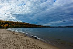 Sand coast in Pictured Rocks National Lakeshore, USA. Sand coast in Pictured Rocks National Lakeshore, Munising, MI, USA. Logs on the foreground. Autumn forest Stock Photo