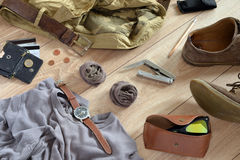 Sand-colored clothes lie on the wooden floor. Sand-colored clothes and accessories lie on the wooden floor Royalty Free Stock Photos