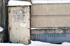 The sand-colored door with torn scraps of old paper ads in which recognizable only single letters, entrance in gray wall with wire. S along, snow on roof and royalty free stock photography