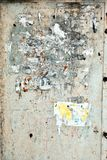 The sand-colored plaster on the wall with torn scraps of old paper ads in which recognizable only single letters. Grunge texture background, vertical royalty free stock photo