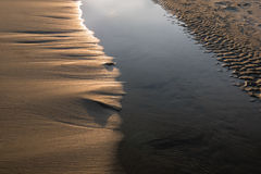 Sand crest on the beach at sunset. Several small waves wide area Stock Photo