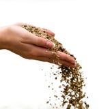 Sand in den weiblichen Händen Lizenzfreies Stockbild