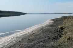 Sand deposits and algae at the shores of Lake Magadi. Sand deposits and colorful algae at the shores of lake magadi against a mountain background, magadi, rift stock image