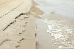 Sand, der durch einen Strom abgefressen wird Stockbild