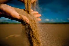 Sand, der durch Hände leckt Lizenzfreie Stockfotos