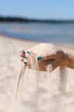 Sand, der durch weibliche Hände läuft Lizenzfreie Stockfotografie