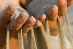Sand, der Finger durchfließt Stockfoto
