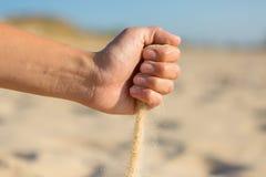 Sand, der von der Faust fällt Lizenzfreies Stockfoto