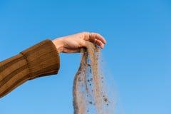 Sand, der von der Hand der Frau fällt Stockbilder
