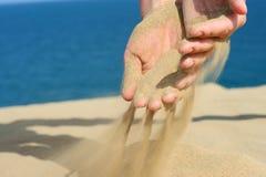 Sand in der weiblichen Hand Lizenzfreies Stockfoto