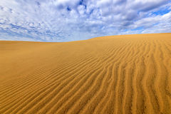Sand desert with beautiful rare blue sky with white clouds. Summer dry landscape in Africa. Sand waves in the wild nature. Dunas M Stock Photo