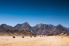 Sand desert, Egypt. Safari Tours by quad bike in Egypt. Tourists riding quadbikes in desert Royalty Free Stock Photos