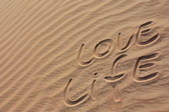 Sand in a desert LOVE LIFE. Yellow sand shaped like waves of the ocean in dubai desert with words written on it stock photography