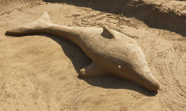 Sand dolphin sculpture stock image