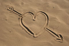 Sand drawn heart and arrow. A view of a drawing in the sand of a heart with an arrow through it Stock Images