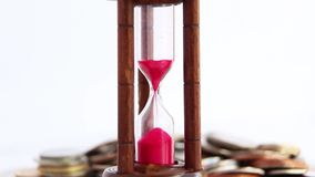 Sand dropping through the bulb of the hourglass and foreign currency coins on the background. The concept of business growth, financial stock video footage