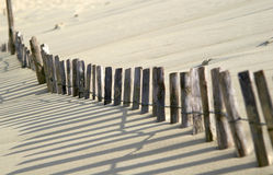 Sand dune. Wooden fence swamped and almost covered by encroaching sand dune stock photos