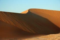 Sand dune. Desert sand dune against clear blue sky Royalty Free Stock Photo