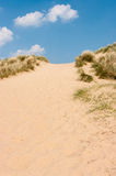 Sand dunes against a blue sky on a sunny day. High sand dunes on a sunny day in Burnham Overy Staithe Norfolk United Kingdom Stock Image