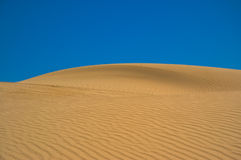 Sand dune against the sky. Royalty Free Stock Photography