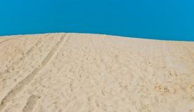 Sand dune on blue sky background. Sand dune with footprints on blue sky background Stock Photo