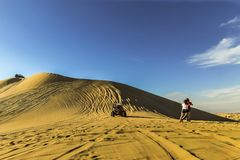 Sand dune buggy racing down the slope as tourists moving aside stock image