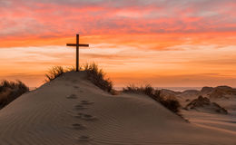 Sand Dune Cross. Black cross on a sand dune with foot steps leading up to it Stock Photos