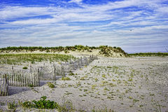 Sand dune, dune fence, and blue sky on Breezy Poin Stock Photography