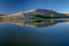 Sand dune on the edge of a small lake. Desert lake and sand dune Royalty Free Stock Images