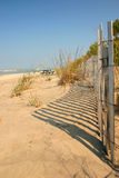 Sand Dune and Fence. With shadows and seagrass Stock Image