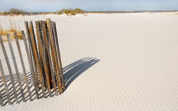 Sand dune fence by rippled sand Royalty Free Stock Images