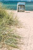 Sand dune with grass and blue colored roofed chairs on sandy beach in Background. Travemunde. Germany Stock Photo