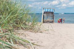 Sand dune with grass and blue colored roofed chairs on sandy beach and blurred kids in Background. Travemunde. Germany.  Royalty Free Stock Photography