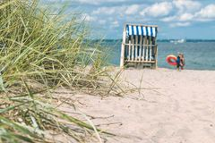 Sand dune with grass and blue colored roofed chairs on sandy beach and blurred kids in Background. Travemunde. Germany Royalty Free Stock Images