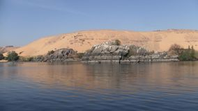 Sand dune and rocks on the bank of the River Nile in Egypt. Sand dune and grey rocks adjacent to the water of the River Nile in Egypt on a sunny day stock video