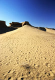 Sand dune with rotten ancient city wall royalty free stock images