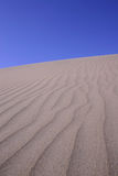 Sand Dune Series. Vertical photo of sand dune and blue sky Royalty Free Stock Photos