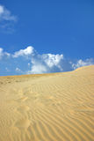 Sand Dune and Sky. Large sand dune reaches to the sky, footprints seen in dune Royalty Free Stock Image