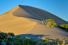 Sand dune at sunrise and blue sky Royalty Free Stock Photos