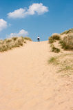 A steep sand dune with a young woman looking over the top on a sunny day Royalty Free Stock Photos