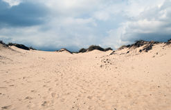 Sand dunes. On a beach in Algeciras, under a sky with clouds Stock Photography