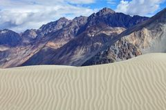 Sand dunes against the Himalayas background Stock Photo