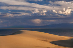 Sand dunes on the background of the desert lake. Royalty Free Stock Photography