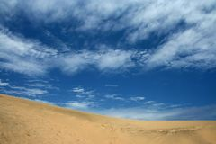 Sand dunes and blue skies. Large dunes agains dark blue skies with some bright clouds Royalty Free Stock Photography