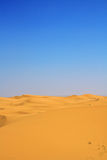 Sand dunes and cloudless blue sky Stock Image